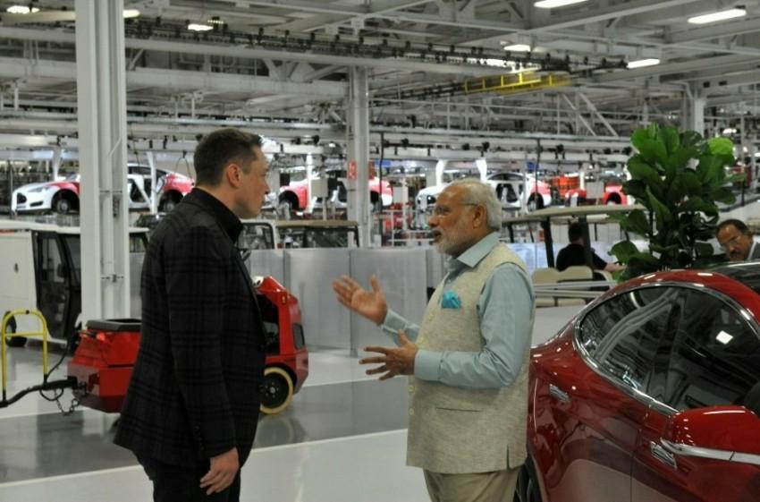 modji talking to Elon musk inside Tesla factory meme template